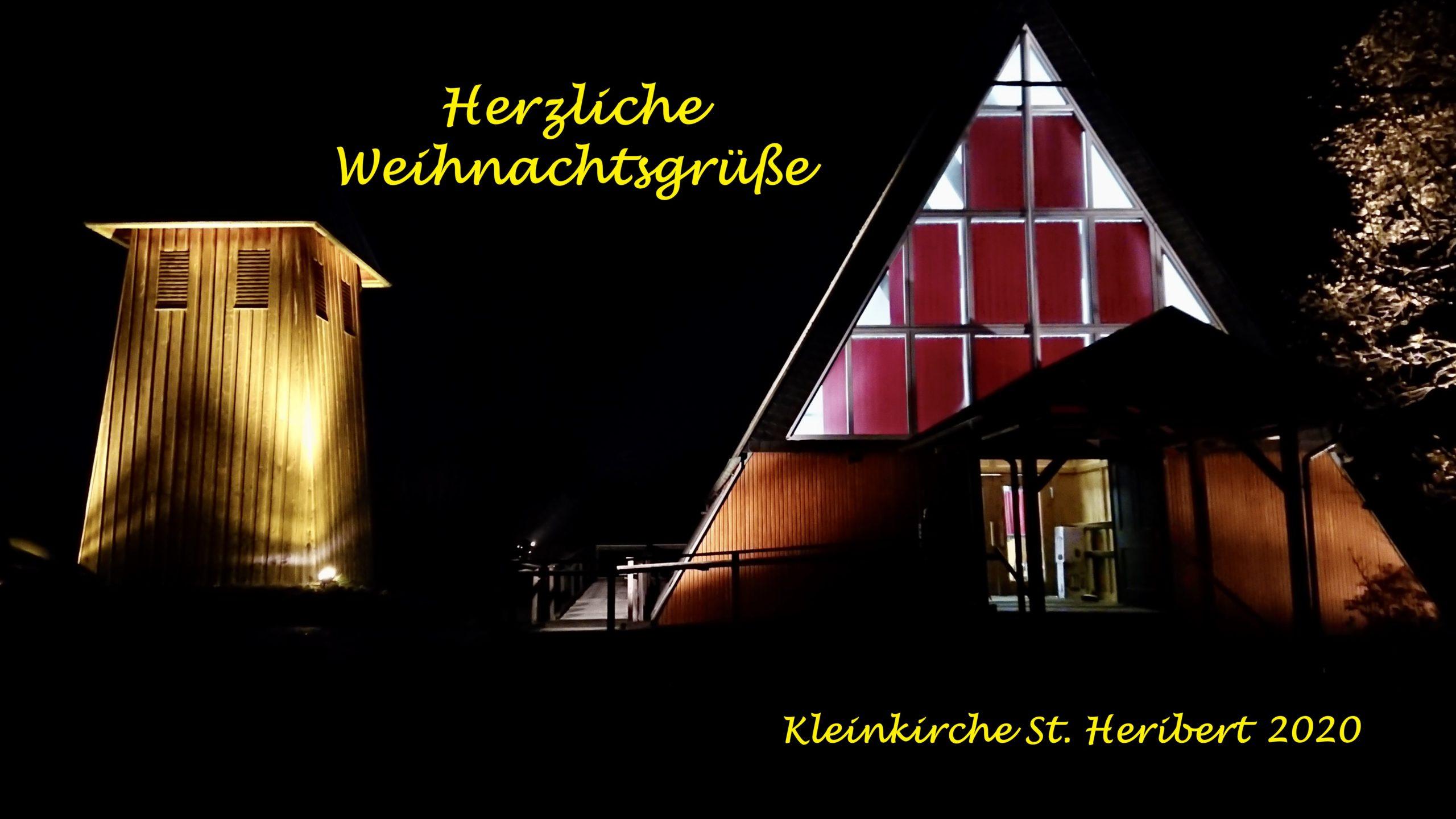 Der Glockenturm und die Kleinkirche St. Heribert bei Nacht und Beleuchtung und der Schriftzug Herzliche Weihnachtsgrüße